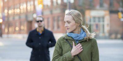 Verängstigte junge Frau mit blondem Haar, die über ihre Schulter auf einen Fremden in einem schwarzen Trenchcoat zurückblickt, der ihr in einer Großstadt folgt.