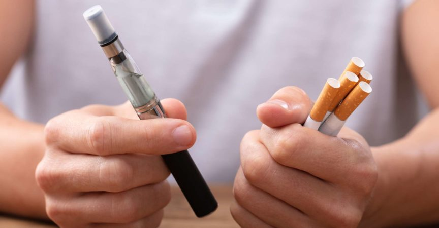 Man Holding Vape And Tobacco Cigarette Over Desk