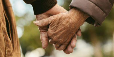 Älteres Paar Händchen haltend und gehend