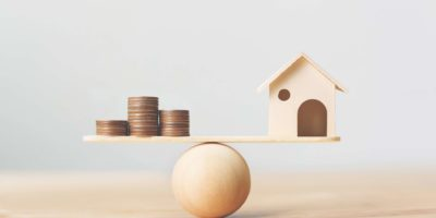 Haus- und Geldmünzen aus Holz stapeln sich auf Holzschuppen. Immobilieninvestment und Haushypothek Finanzimmobilienkonzept