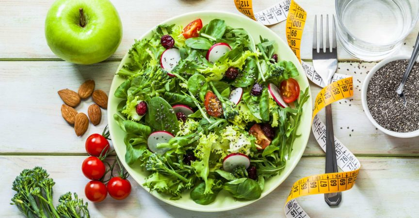 Großer frischer Salat, Apfel und Tomaten. Maßband. Frisches Gemüse. Konzept für Abnehmen und Diät. Vegane Ernährung.
