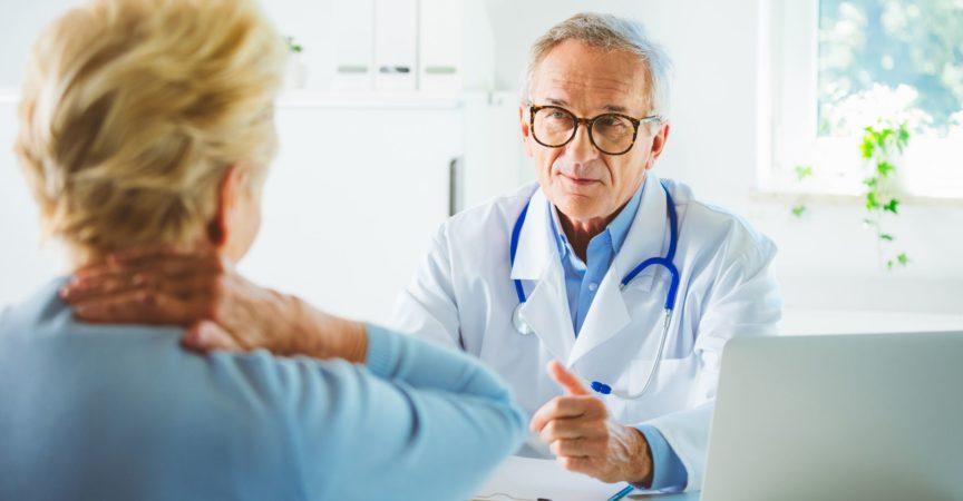 Senior Gesundheitspersonal im Gespräch mit Patientin im Krankenzimmer. Doktor, der der älteren Frau zuhört, die Rückenschmerzen hat.