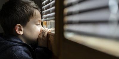 Kleiner trauriger Junge, der durch das Fenster schaut. Konzept zur sozialen Distanzierung bei Coronavirus-Pandemie