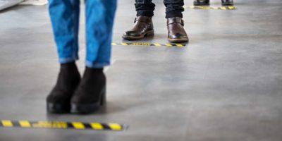 Geschäftsleute, die hinter sozialer distanzierender Beschilderung auf Büroboden stehen