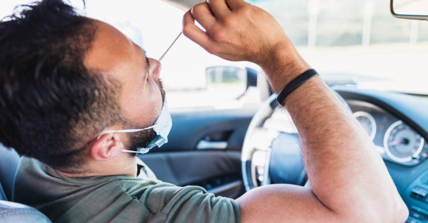 Während er in seinem Auto sitzt, führt ein Mann im mittleren Erwachsenenalter einen Selbst-COVID-Test auf einer Fahrt durch die COVID-Teststelle durch.