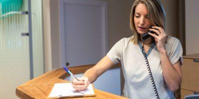 junge Frau Empfangsdame tragen und schreiben Anrufbeantworter an der Rezeption des modernen Fitnessclubs oder Gesundheitszentrums