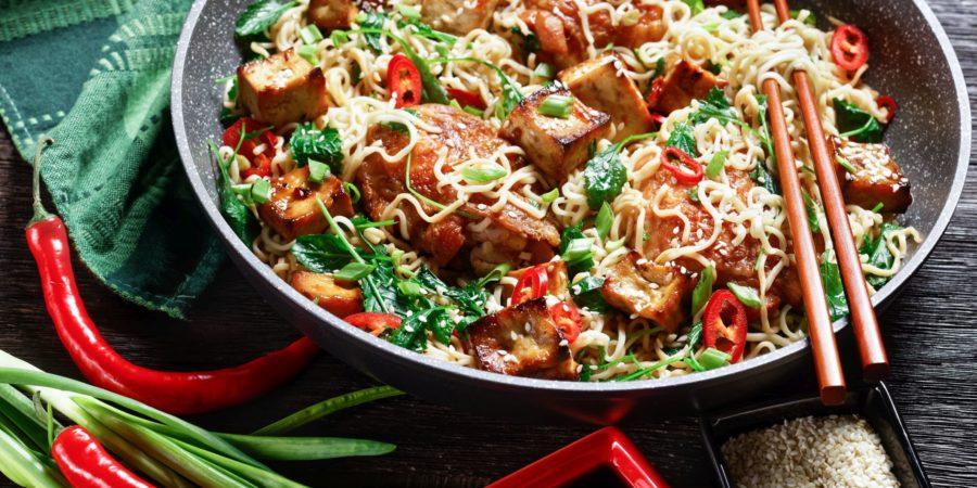 Süß-saurer Tofu, Hähnchenschenkel, chinesische Woknudeln, verwelkter Grünkohl, Sesam, roter Chili, Frühlingszwiebeln, serviert auf einer Pfanne mit Stäbchen auf dunklem Holzhintergrund, Draufsicht, Nahaufnahme