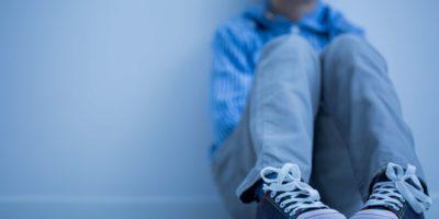 Trauriger Junge in Turnschuhen mit Asperger-Syndrom sitzt alleine in seinem Zimmer