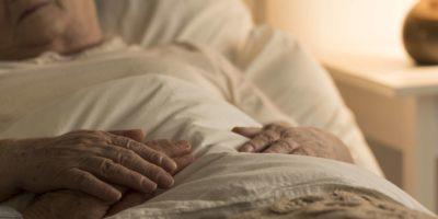Nahaufnahme der Hand des Senioren auf der Hand der sterbenden älteren Person als Zeichen der Unterstützung während der Krankheit