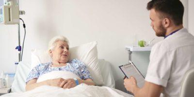 Ältere Frau Seniorin im Bett spricht mit ihrem Arzt