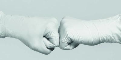 Weiße Handschuhe zum Modell. Kampf gegen das Coronavirus. Zwei medizinische Arbeiter machen eine Fauststoßgeste.