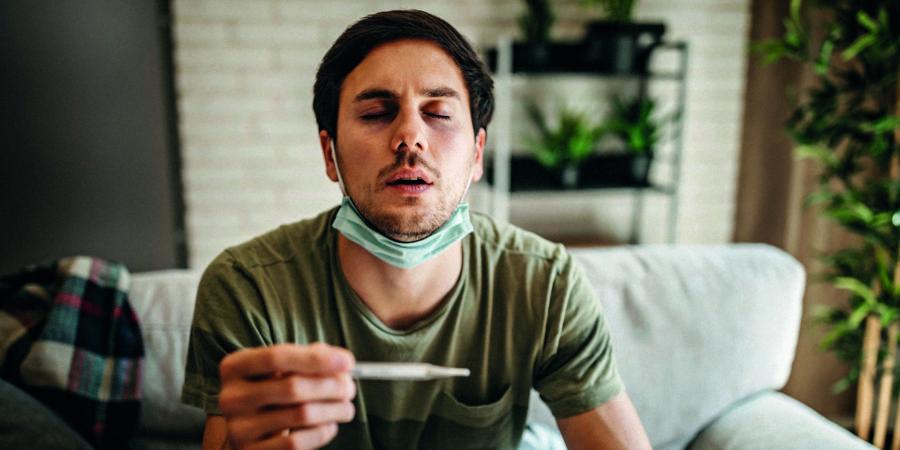 Mann im Bett liegend, erkältet er sich