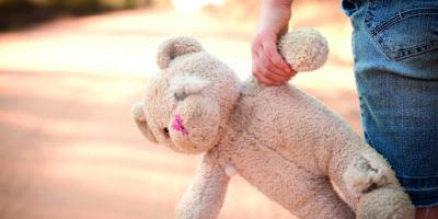 Farbiges Foto auf Lager eines kleinen außer Kontrolle geratenen Mädchens, das einen alten Teddybär an der Seite einer unbefestigten Straße im ländlichen Land hält.
