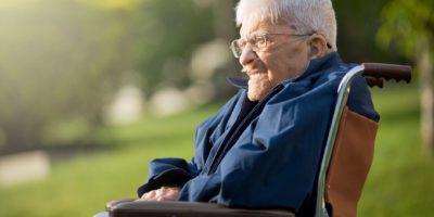 Ein 92 Jahre alter Mann sitzt in seinem Rollstuhl und genießt die Abendsonne.