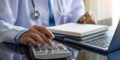Ärztin mit Taschenrechner und Notebook am Schreibtisch im modernen Büro in der Klinik oder im Krankenhaus