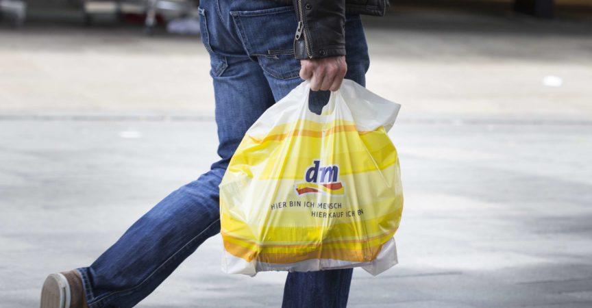 Ein unkenntlicher Fußgänger mit einer Plastiktüte vom dm-Drogeriemarkt im Vorbeigehen in einer Einkaufsstraße in der Wiesbadener Innenstadt. dm-drogerie-markt ist eine Drogeriemarktkette für Kosmetik, Gesundheits- und Haushaltsprodukte sowie Lebensmittel.