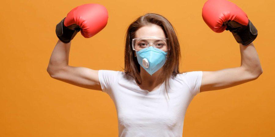 woman in boxing gloves, home quarantine, coronavirus pandemic, on yellow orange background, battle fight with virus