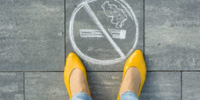 Female feet with picture no smoking painted on the grey sidewalk.