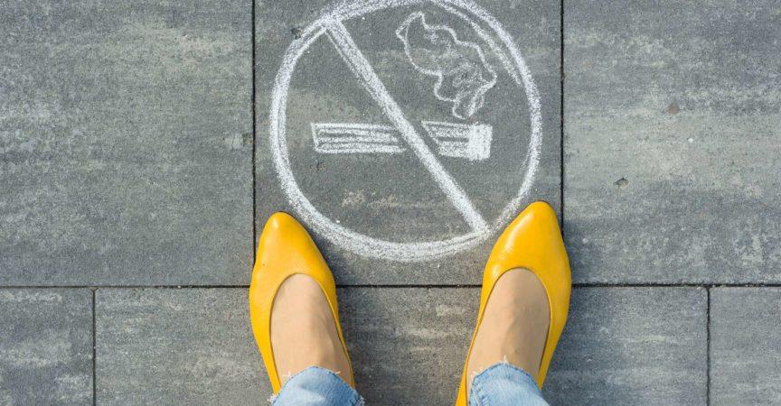 Weibliche Füße mit Rauchverbots-Bild auf dem grauen Bürgersteig gemalt.