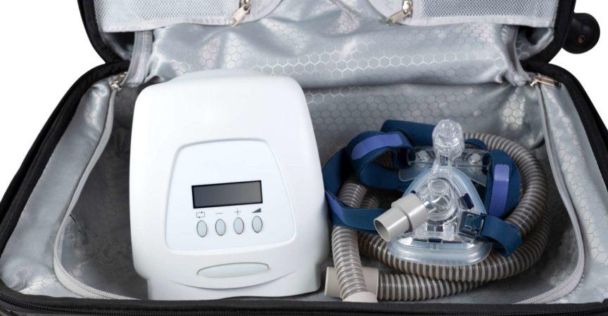 CPAP-Maschine, die in Reisetasche bereit für eine Reise, weißer Hintergrund legt.