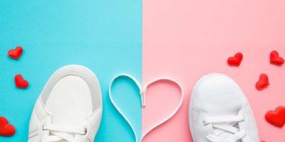 Herz aus weißen Schnürsenkeln zwischen männlichen und weiblichen Sportschuhen. Helle, rote Herzen. Liebeskonzept. Leerer Platz für schönen, niedlichen Text, Zitat oder Sprüche auf pastellblauem und rosa Papier. Nahansicht.