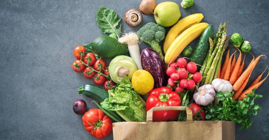 Gesunde Auswahl an Lebensmitteln. Einkaufstasche voller frischem Gemüse und Obst. Flach lag Essen auf dem Tisch