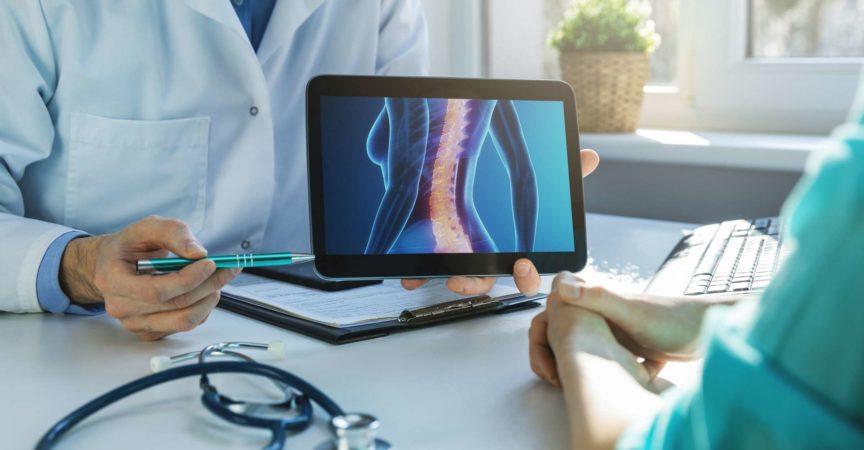 Arzt und Patient sprechen über die Behandlung von Rückenschmerzen im Klinikbüro