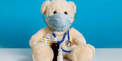 Teddybär Arzt mit medizinischer Maske, Stethoskop und Medizin. Konzept der Hygiene und des Virenschutzes für Kinderpatienten