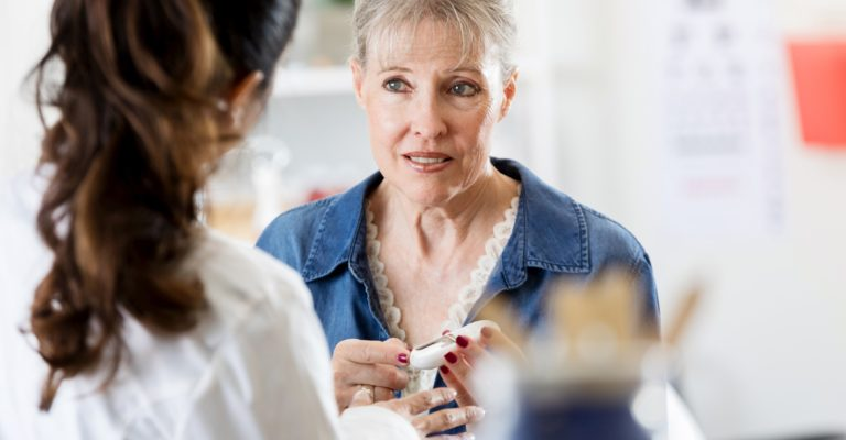 Eine betroffene ältere Frau hält ein Glaukometer in der Hand, als sie mit einer Ärztin über ihre Diabetesdiagnose spricht.