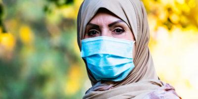 Lächelnde reife nahöstliche muslimische Frau, die die Kamera mit einer schützenden Gesichtsmaske betrachtet