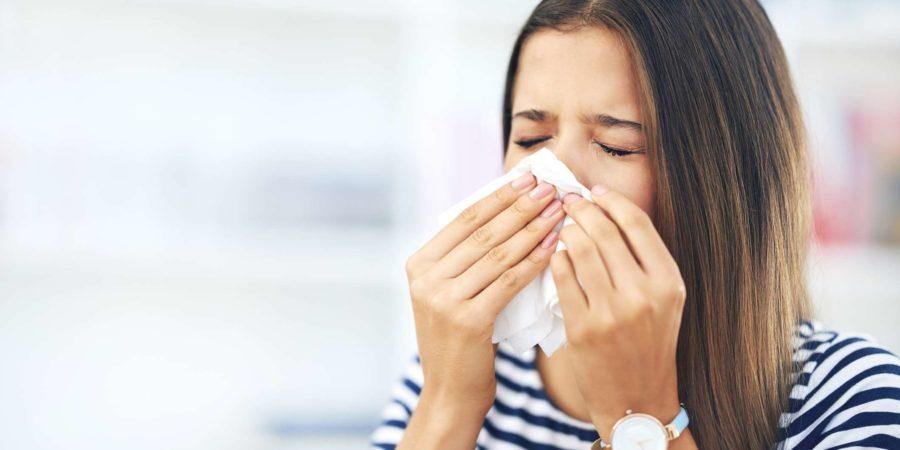 Aufnahme einer jungen Frau mit Allergien, die zu Hause in ein Taschentuch niest