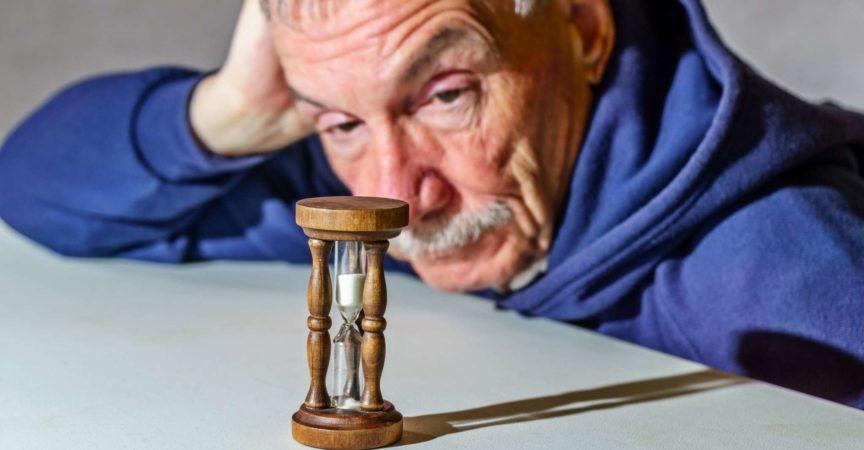 Älterer Mann, der beobachtet, wie eine Zeit vergeht, während Sand durch eine Sanduhr fällt