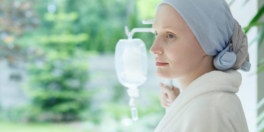 Junge Frau mit Hautkrebs, die auf einem Tropfen im Krankenhaus steht