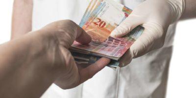 Arzt erhält eine große Menge Schweizer Banknoten als Bestechung. Korruption im Gesundheitswesen.