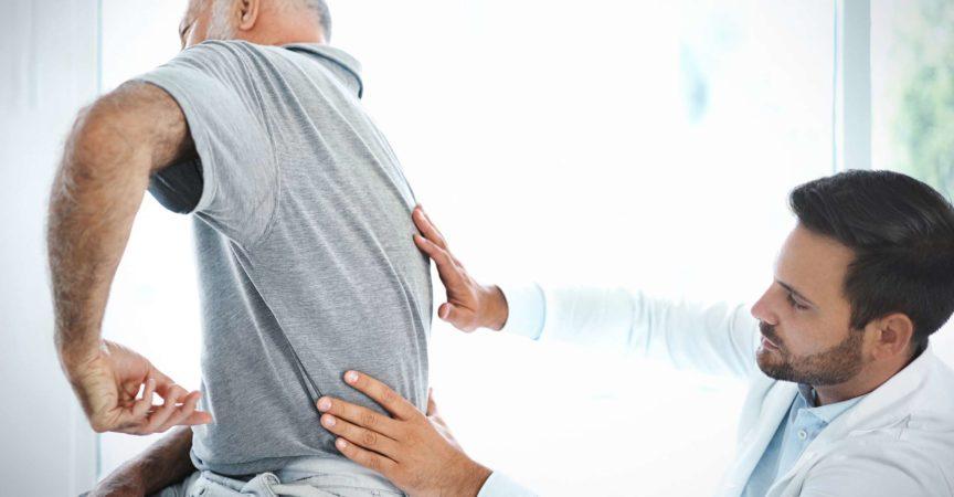 Älterer Mann, der seinen Rücken von einem Arzt untersuchen lässt.