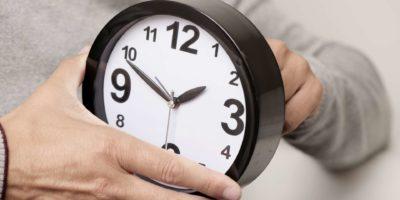 Nahaufnahme eines jungen kaukasischen Mannes, der die Zeit einer Uhr einstellt