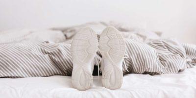 Junge, weibliche Beine in weißen Turnschuhen, am Bett liegend