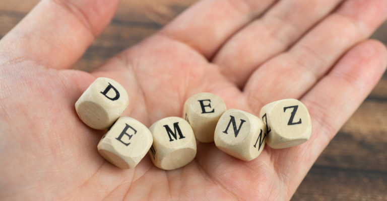 Hand with wood cubes and the German word for dementia, wooden background