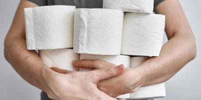 Die Leute füllen Toilettenpapier für die Heimquarantäne von Crownavirus auf. Frau hält viele Rollen Toilettenpapier