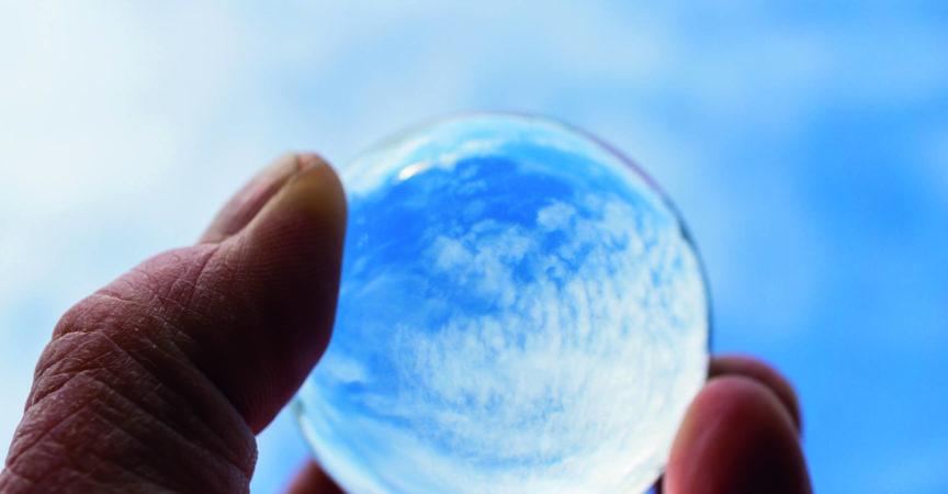 Die Hand eines Psoriasis-Patienten hält eine Glaskugel, in der sich ein blauer Himmel mit Wolken spiegelt. Ein Symbol der Hoffnung auf Genesung. Internationaler Psoriasis-Tag.