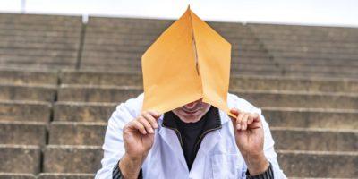 Arbeitsproblem. Allgemeinmediziner oder Zahnarzt, der auf einer Außentreppe sitzt und sein Gesicht mit einer klinischen Studie versteckt