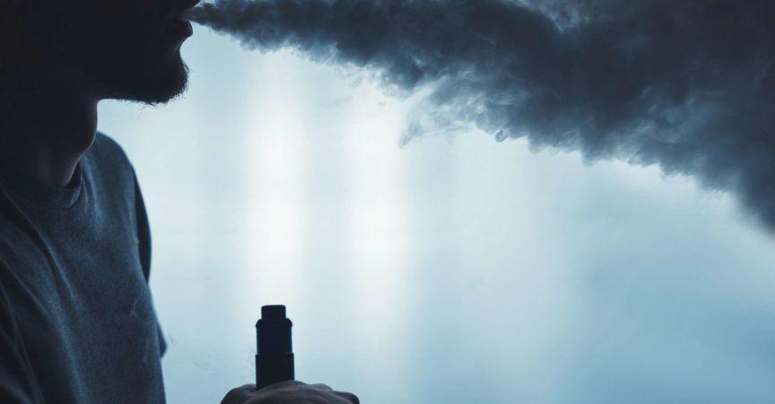 Ein bärtiger Mann in den Dampfwolken von der Nahaufnahme der elektronischen Zigarette. vaping Mann