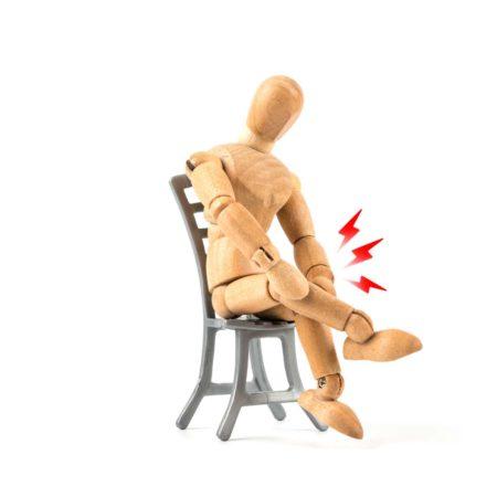 Holzpuppe, die das Knie bei Schmerzen hält - Verletzung oder Arthrose