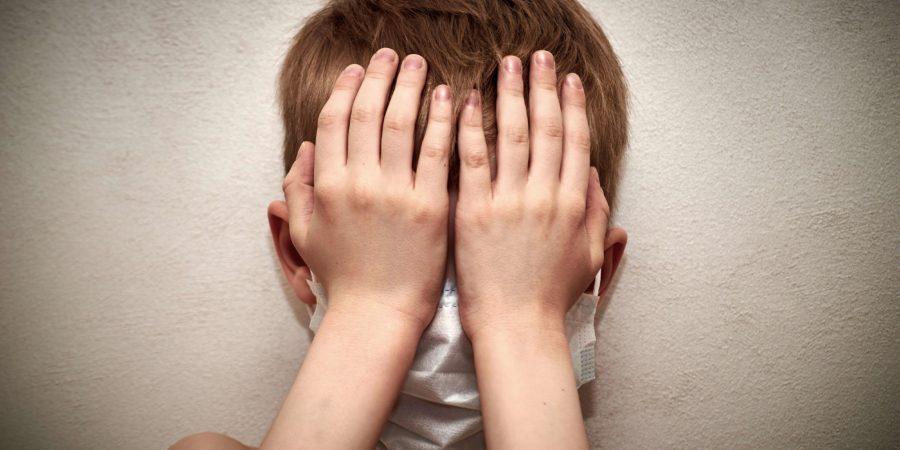 Kleiner Junge hat Angst vor einer Epidemie eines Virus, das sich auf der ganzen Welt ausbreitet. Gesicht eines Jungen in einer Maske zum Schutz vor Infektionen. Globale Epidemie. Angst