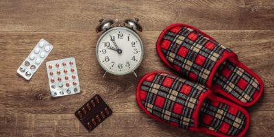 Das Konzept der Schlaflosigkeit. Hausschuhe und Wecker, Pille auf dem Boden. Draufsicht