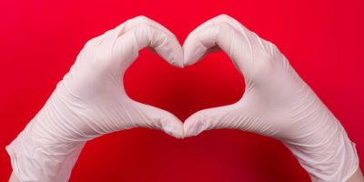 Rette ein Lebenskonzept. Top pov über oben Nahaufnahme Ansicht Foto der Frau, die Herz mit ihren Händen in Handschuhen auf rotem Hintergrund macht