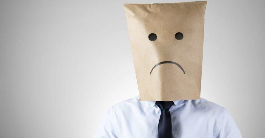 Geschäftsmann trägt eine Papiertüte mit einem traurigen Gesicht Die Wirtschaft hat sein Geschäft nach unten gedrückt.
