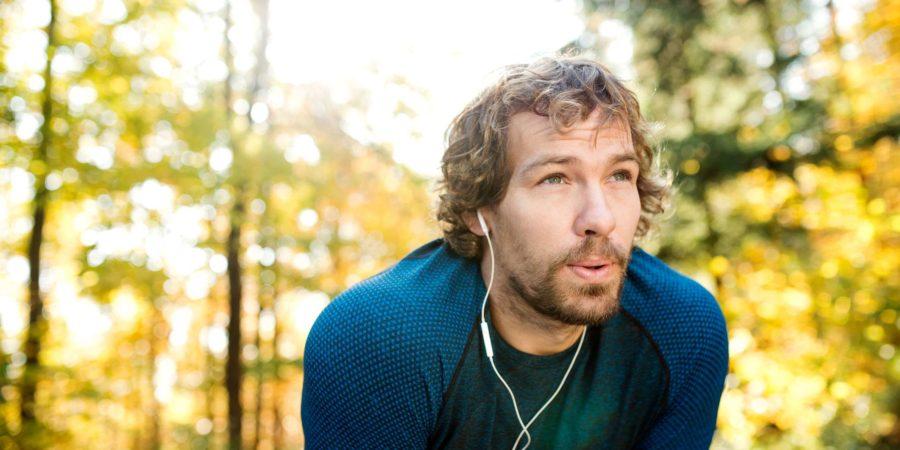 Junger hübscher Läufer mit Kopfhörern in seinen Ohren, Musik hörend, draußen in der sonnigen Herbstnatur, ruhend, ausatmend