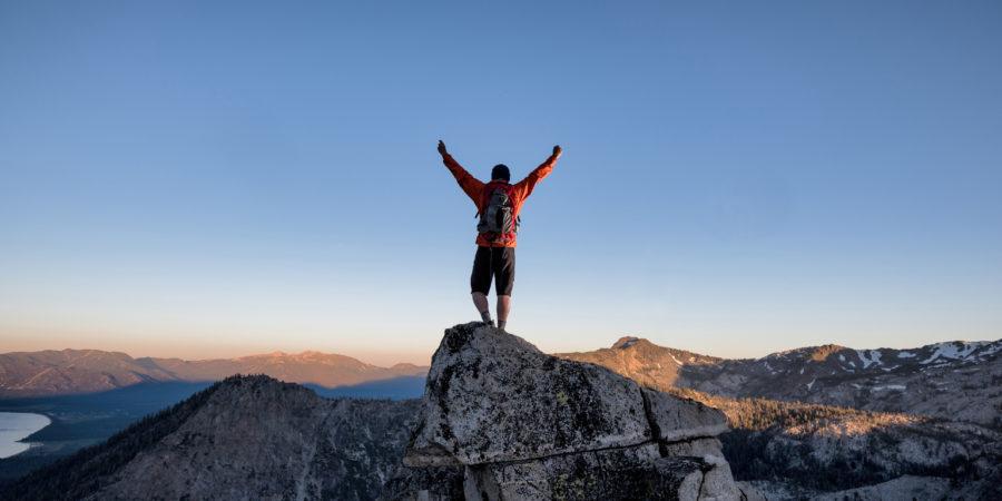 Ein Kletterer erreicht den Gipfel eines exponierten Berggipfels im Hinterland von Tahoe, Kalifornien