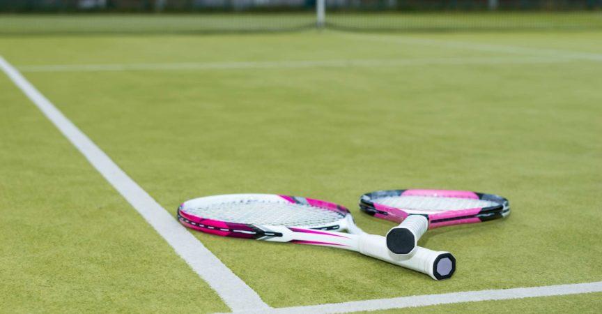 Rosa Tennisschläger, der draußen auf dem Rasenplatz liegt